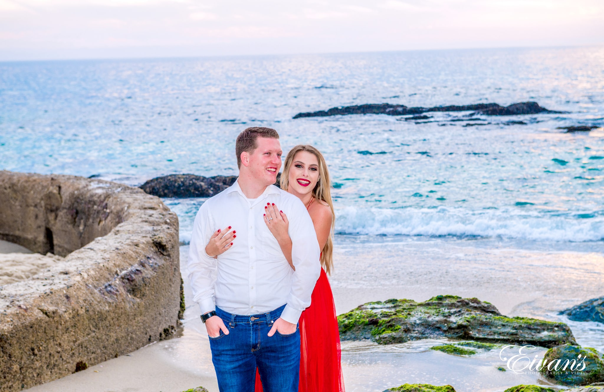 man in white dress shirt beside woman in red dress standing on brown rock near body