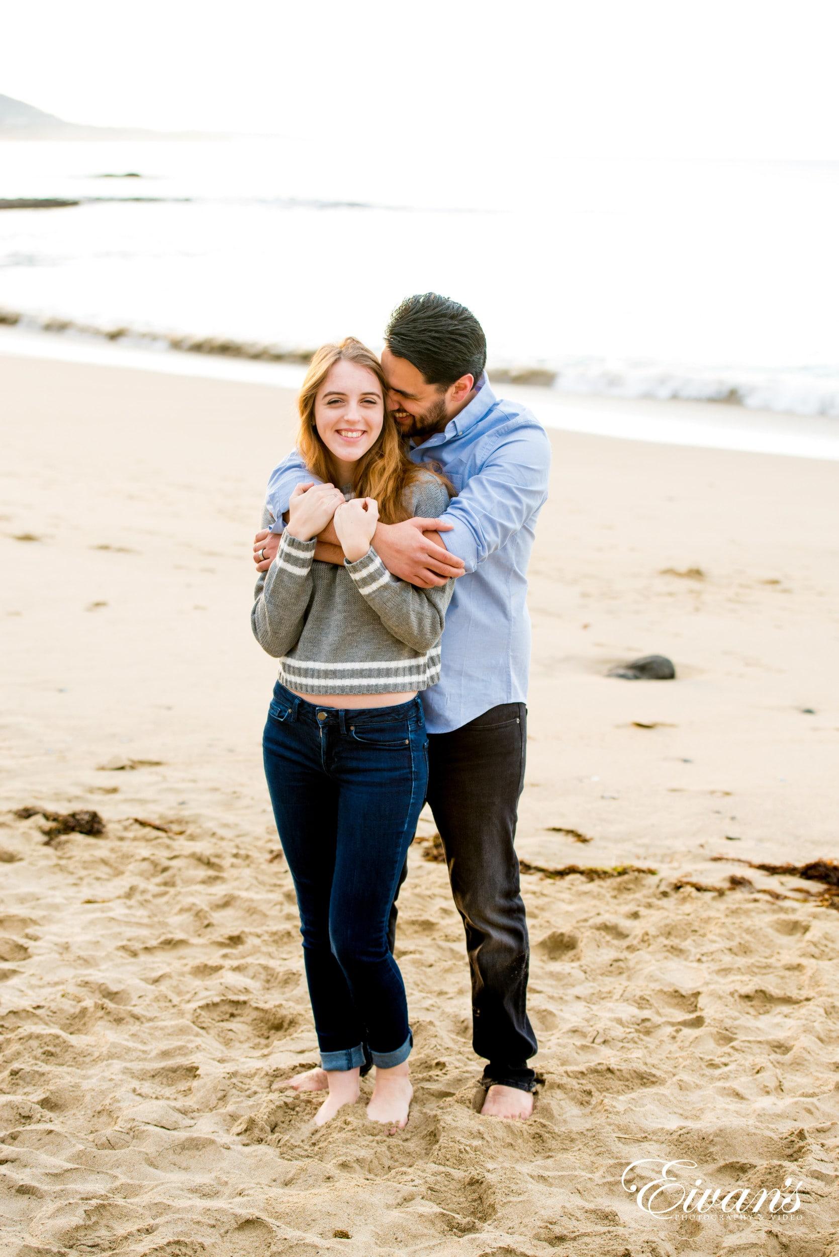 man in gray long sleeve shirt hugging woman in gray long sleeve shirt on beach during