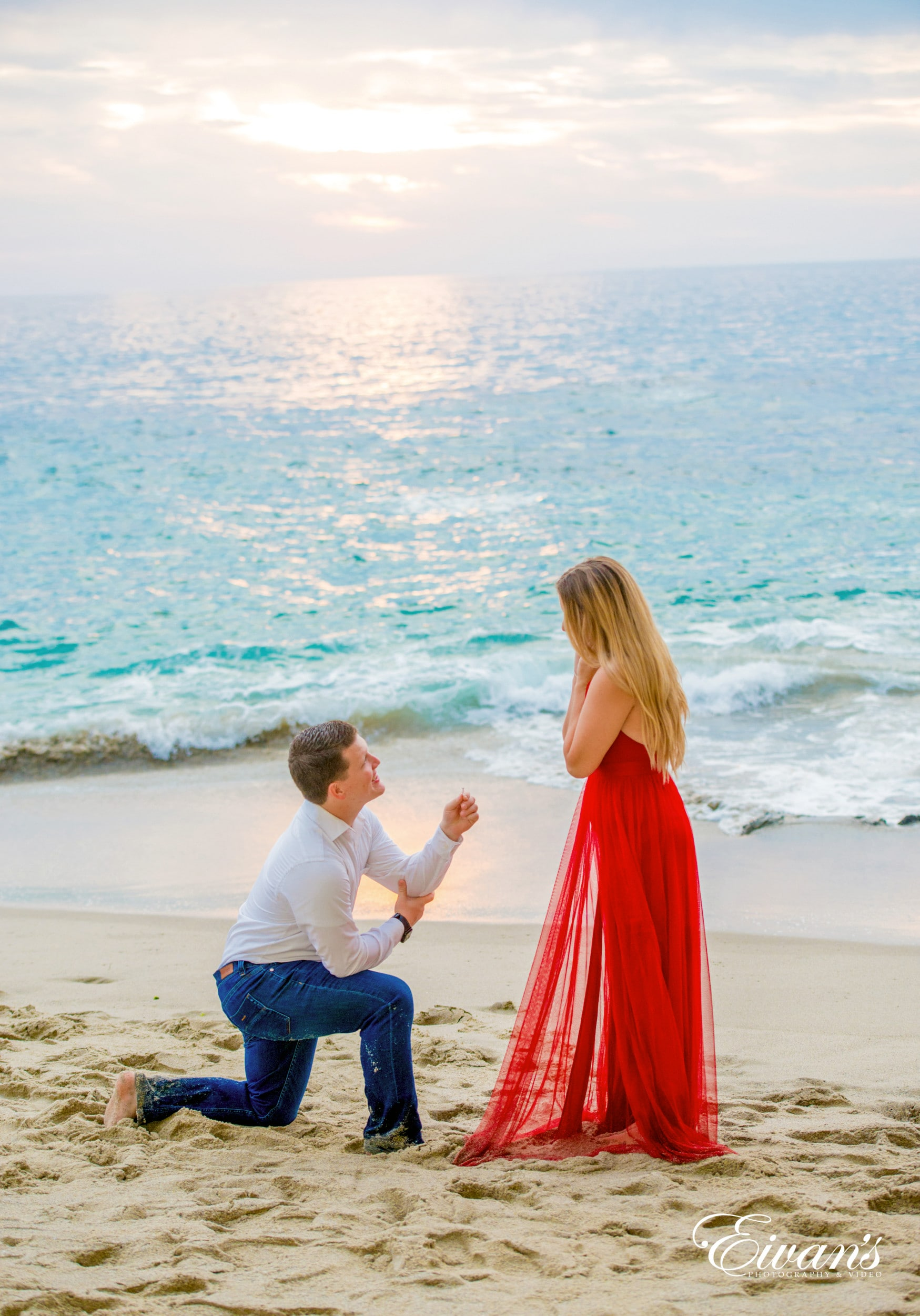 woman in red dress holding man in white dress shirt on beach during daytime