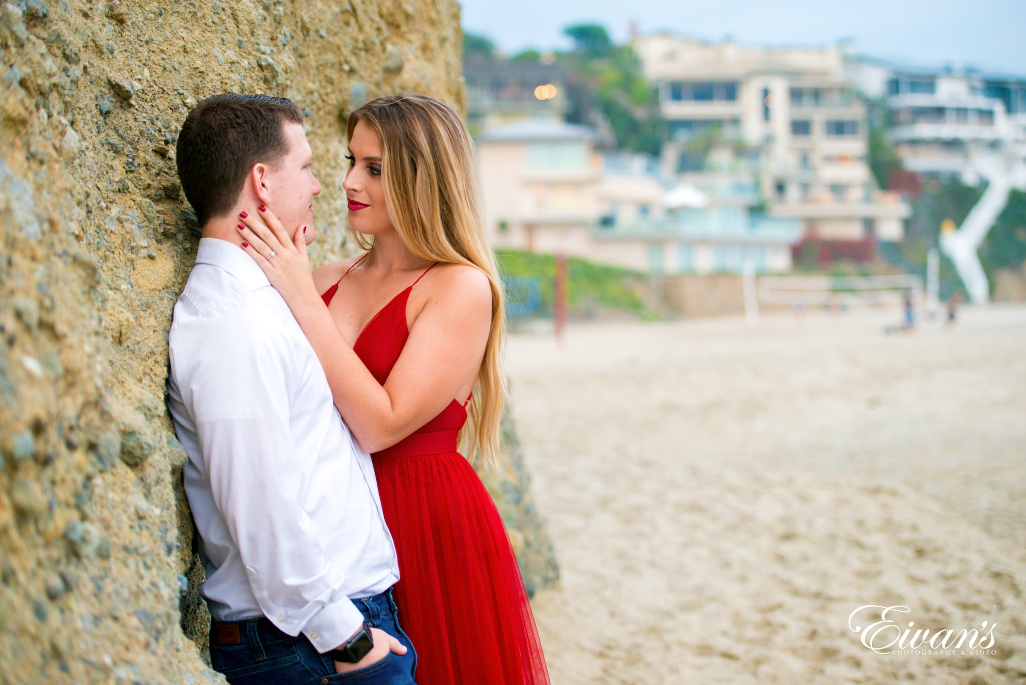 man and woman kissing beside brown rock during daytime