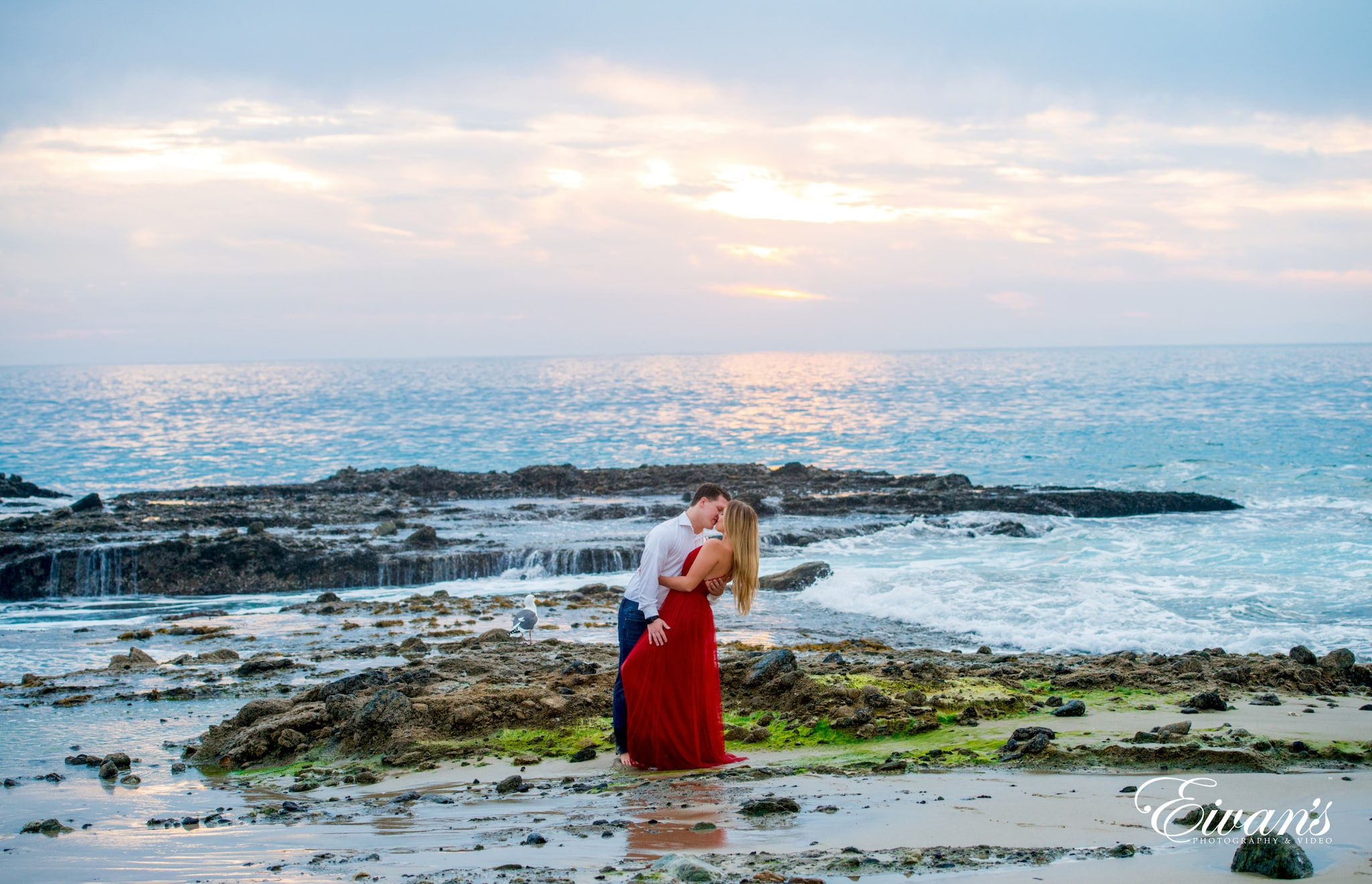 woman in red dress standing on seashore during daytime