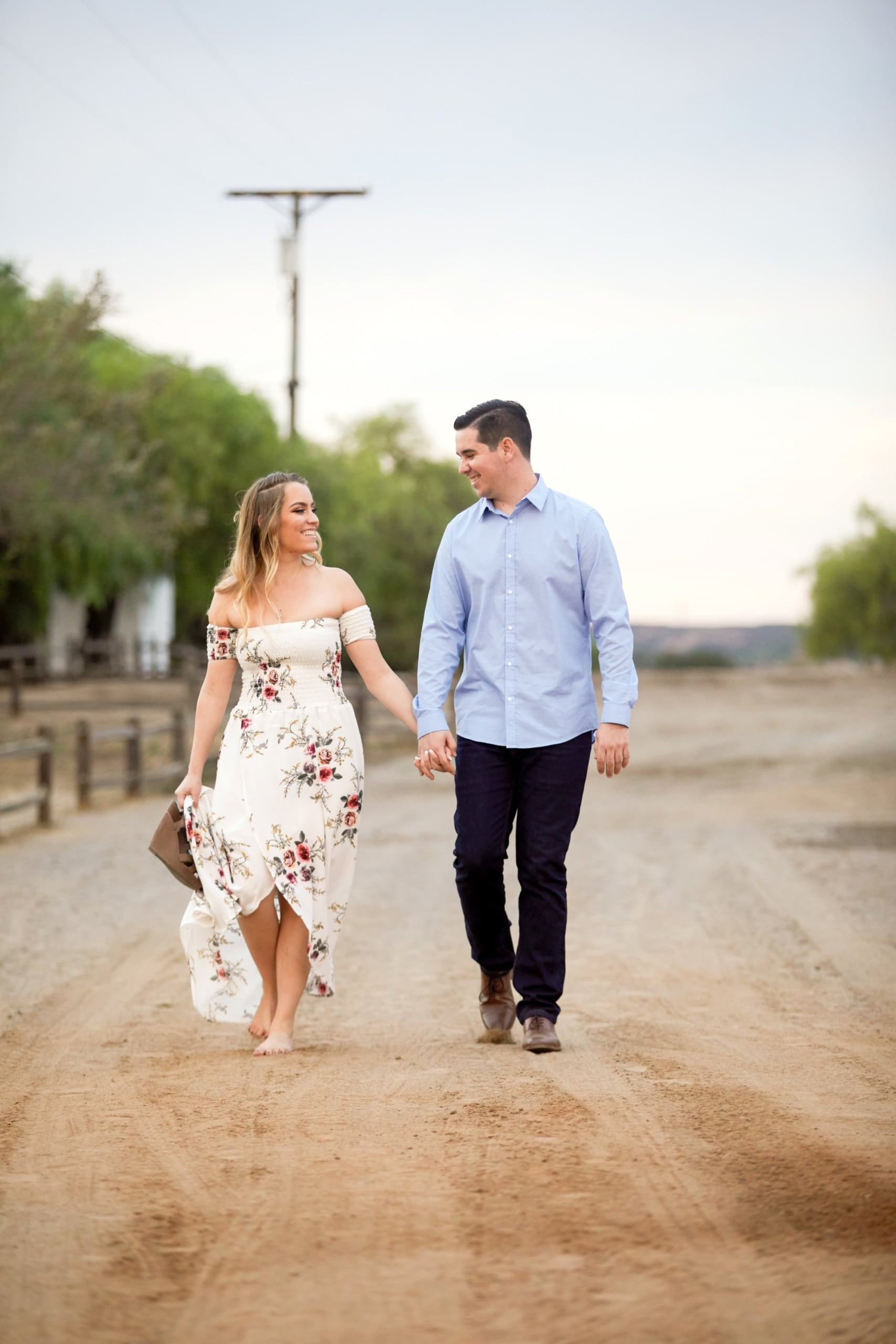 a man and a woman walking down a dirt road