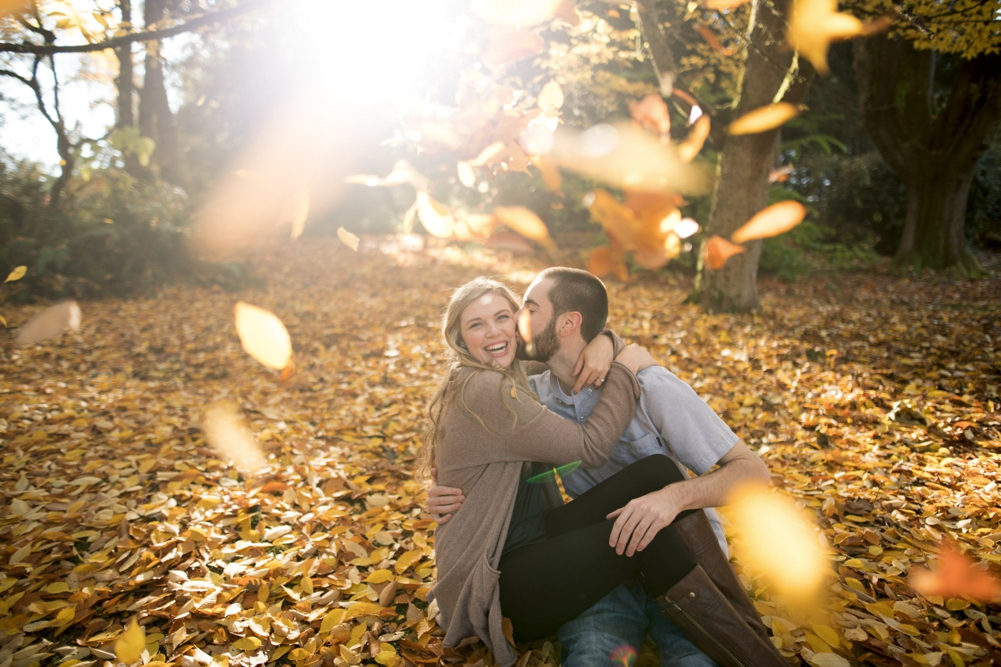 man and woman sitting on ground surrounded by brown leaves during daytime