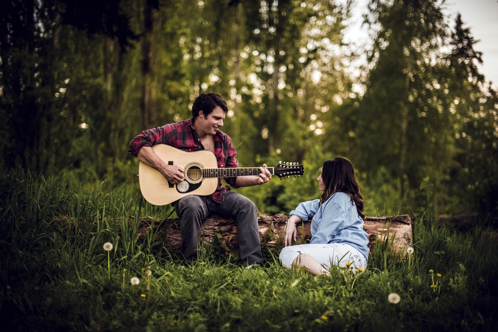 man and woman sitting on grass field playing guitar during daytime