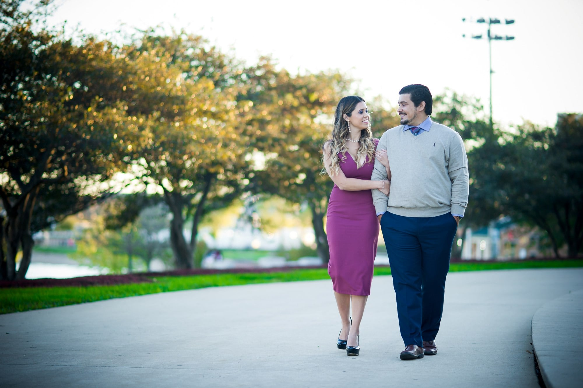 man in gray long sleeve shirt and woman in pink dress standing on gray concrete road