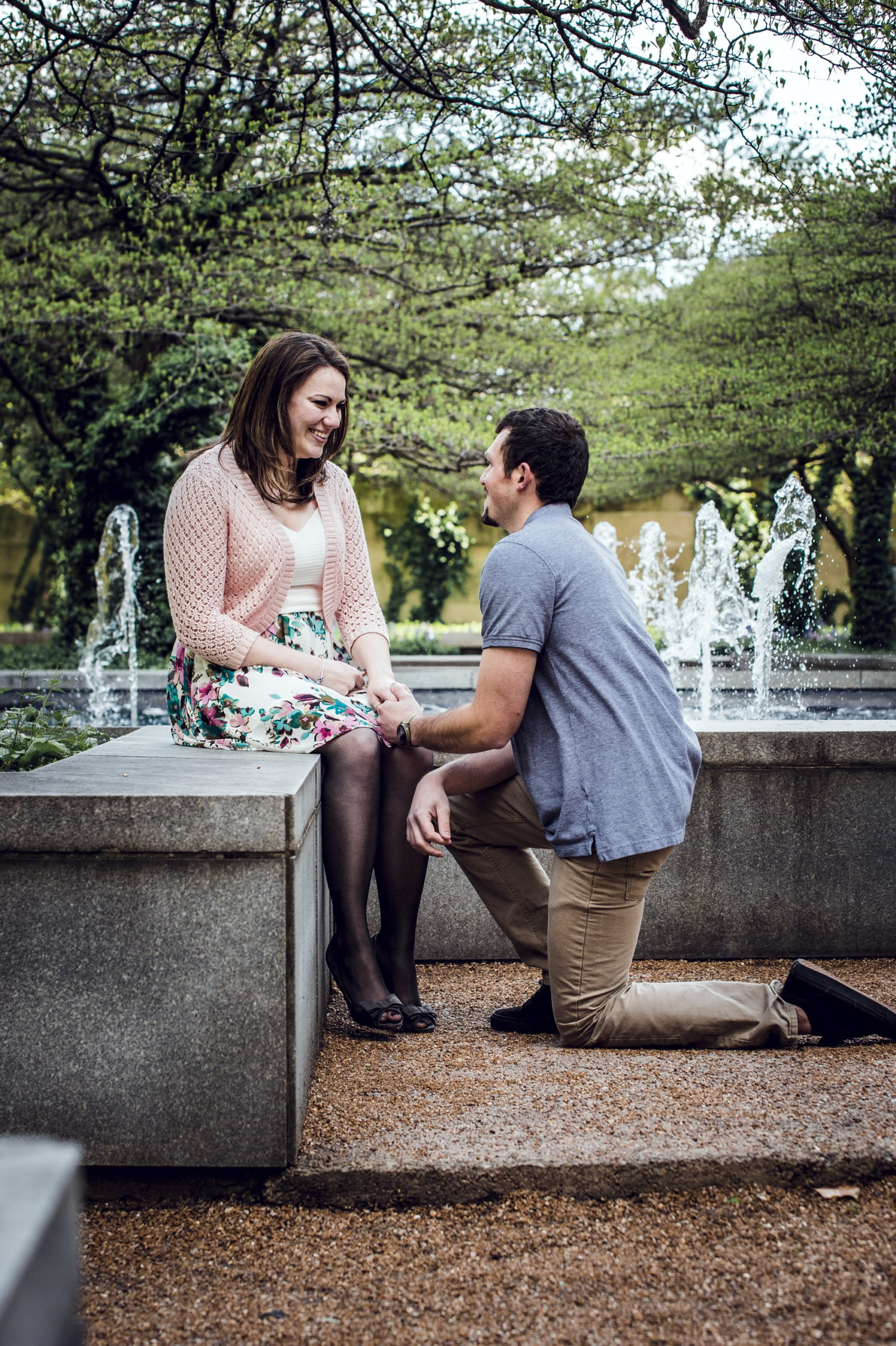 man and woman sitting on concrete fountain during daytime