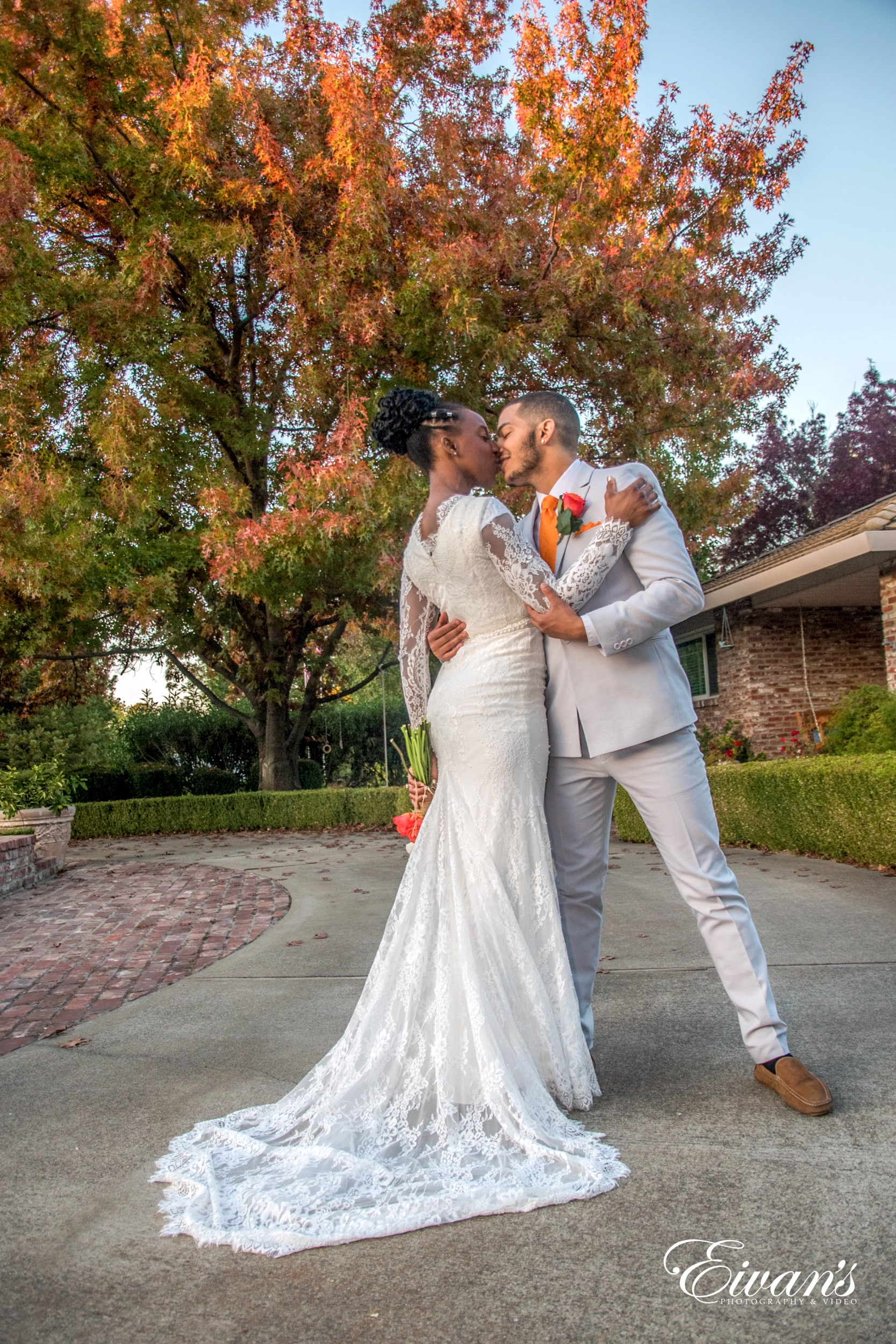 man in white suit kissing woman in white wedding dress on gray concrete pathway during daytime