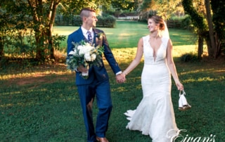 man in black suit and woman in white wedding dress holding bouquet of flowers