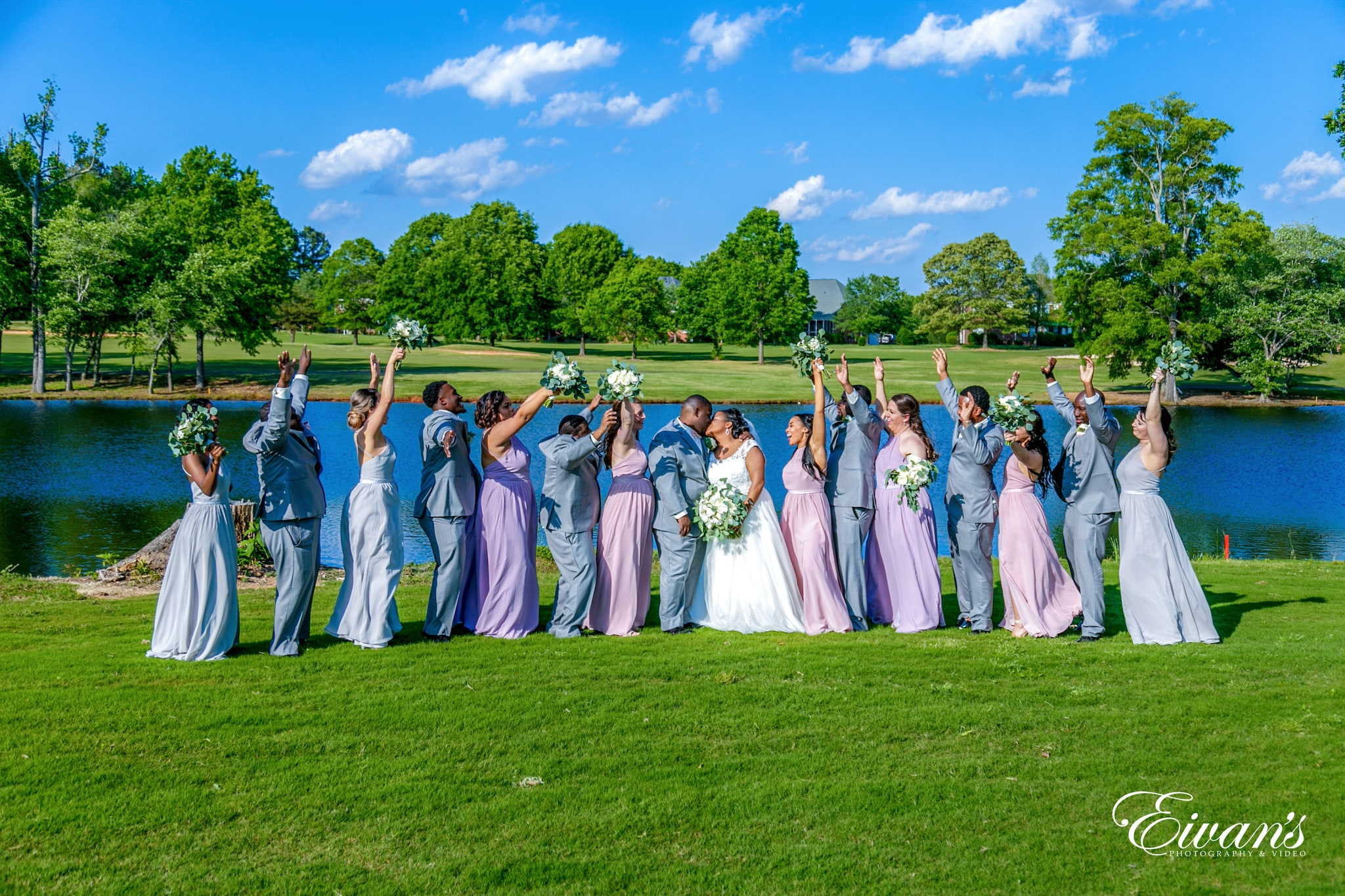 wedding party standing on green grass field during daytime