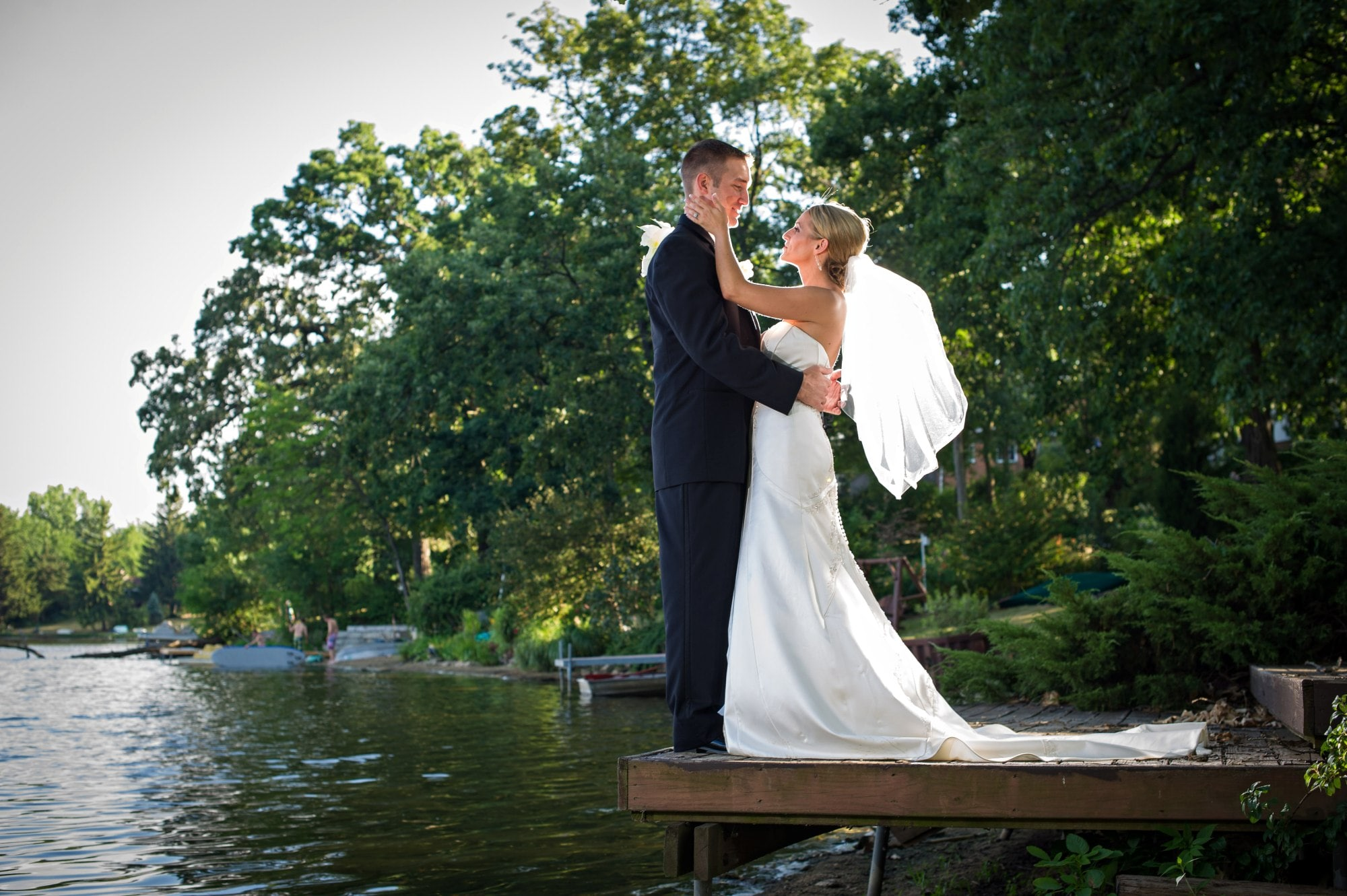 man in black suit kissing woman in white wedding dress on brown wooden dock during daytime