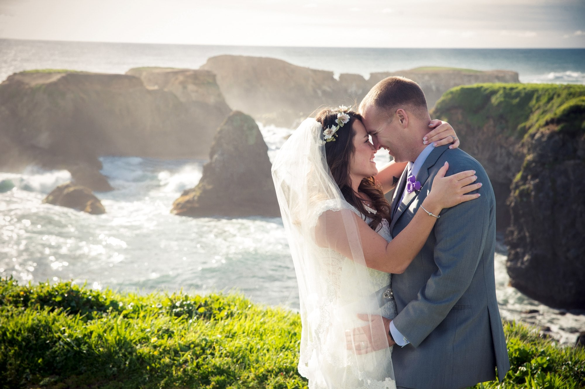 man in gray suit kissing woman in white wedding dress near body of water during daytime