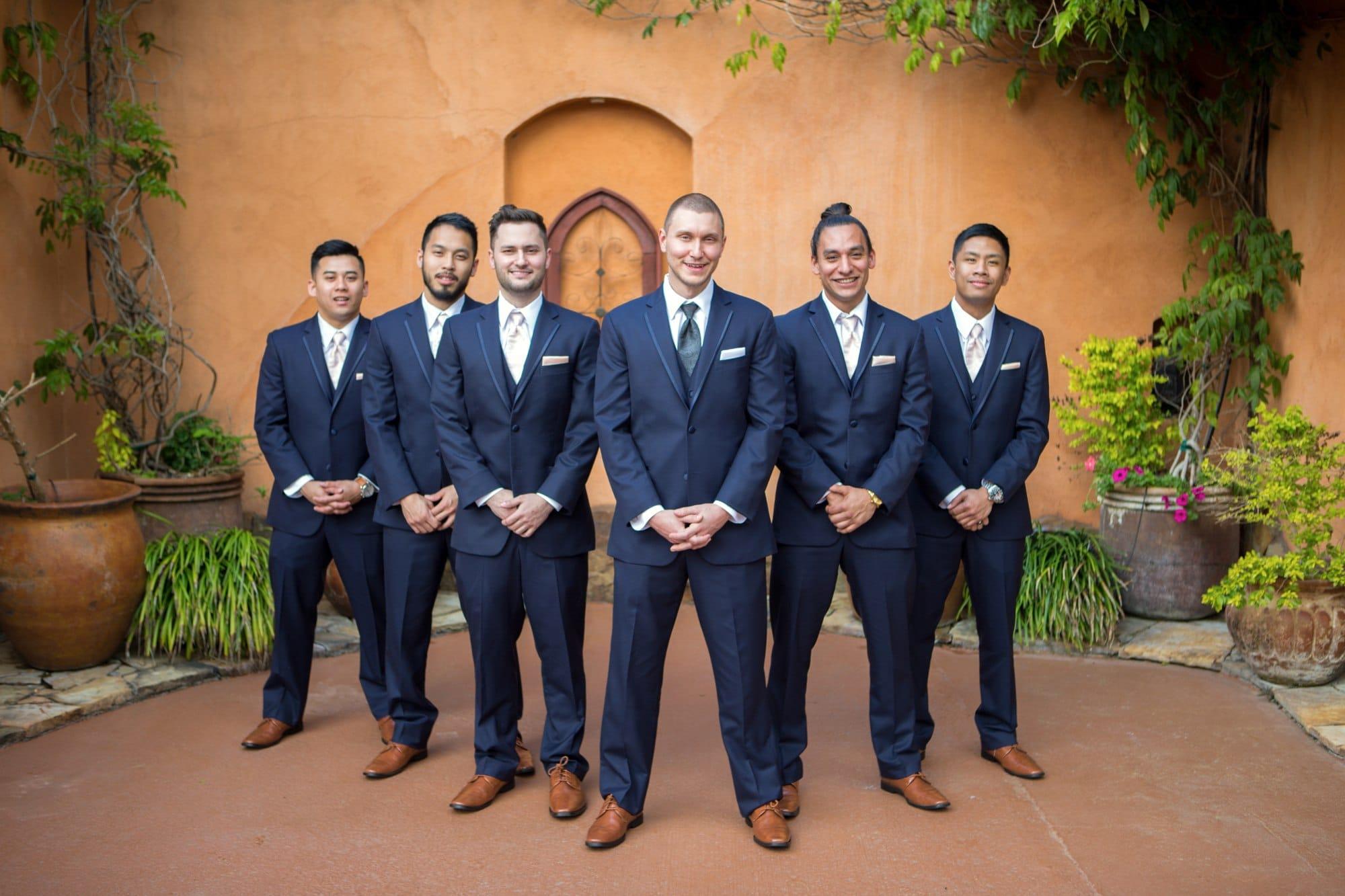 3 men in black suit standing beside brown wall