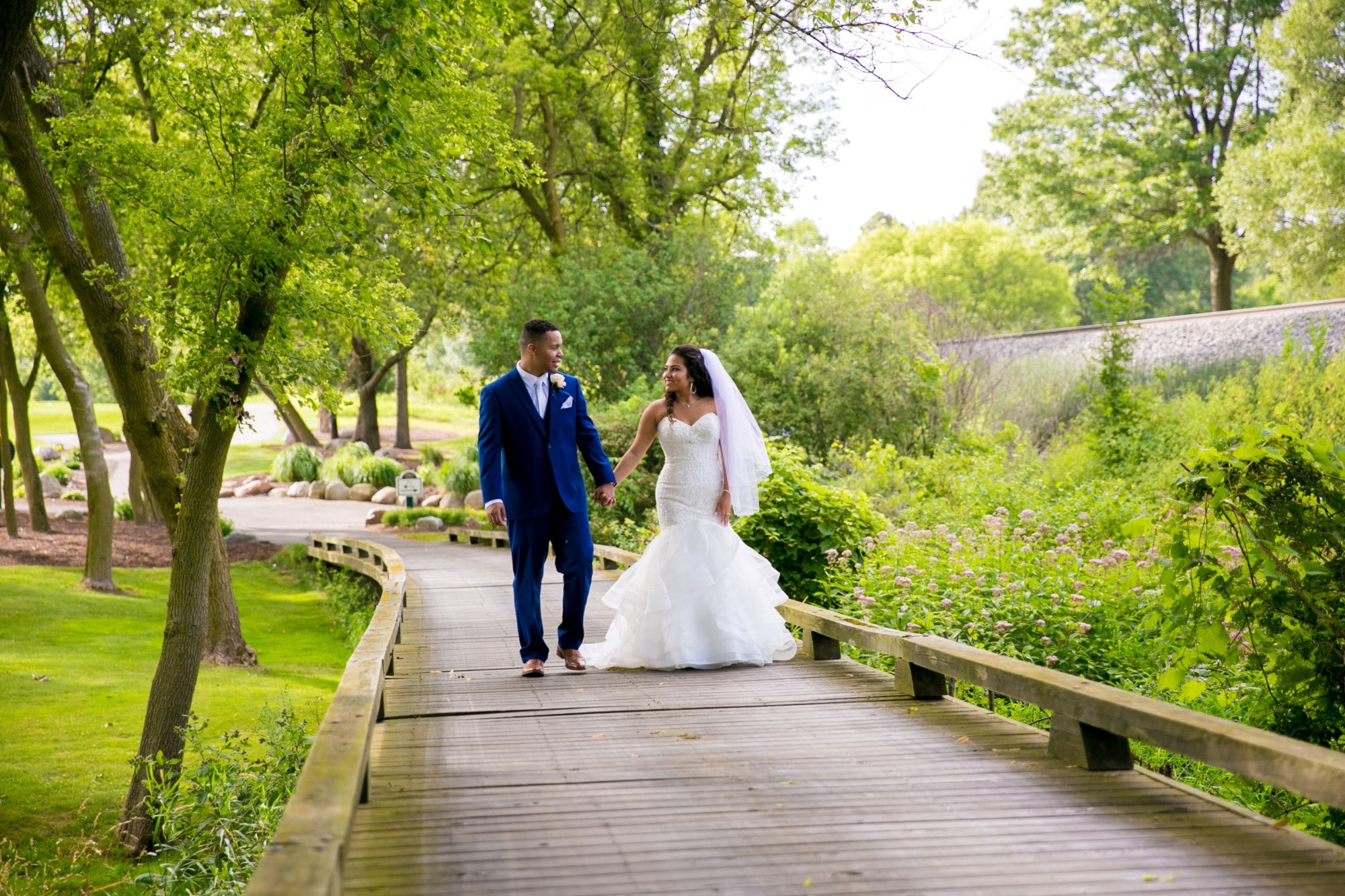 bride and groom walking on wooden bridge during daytime