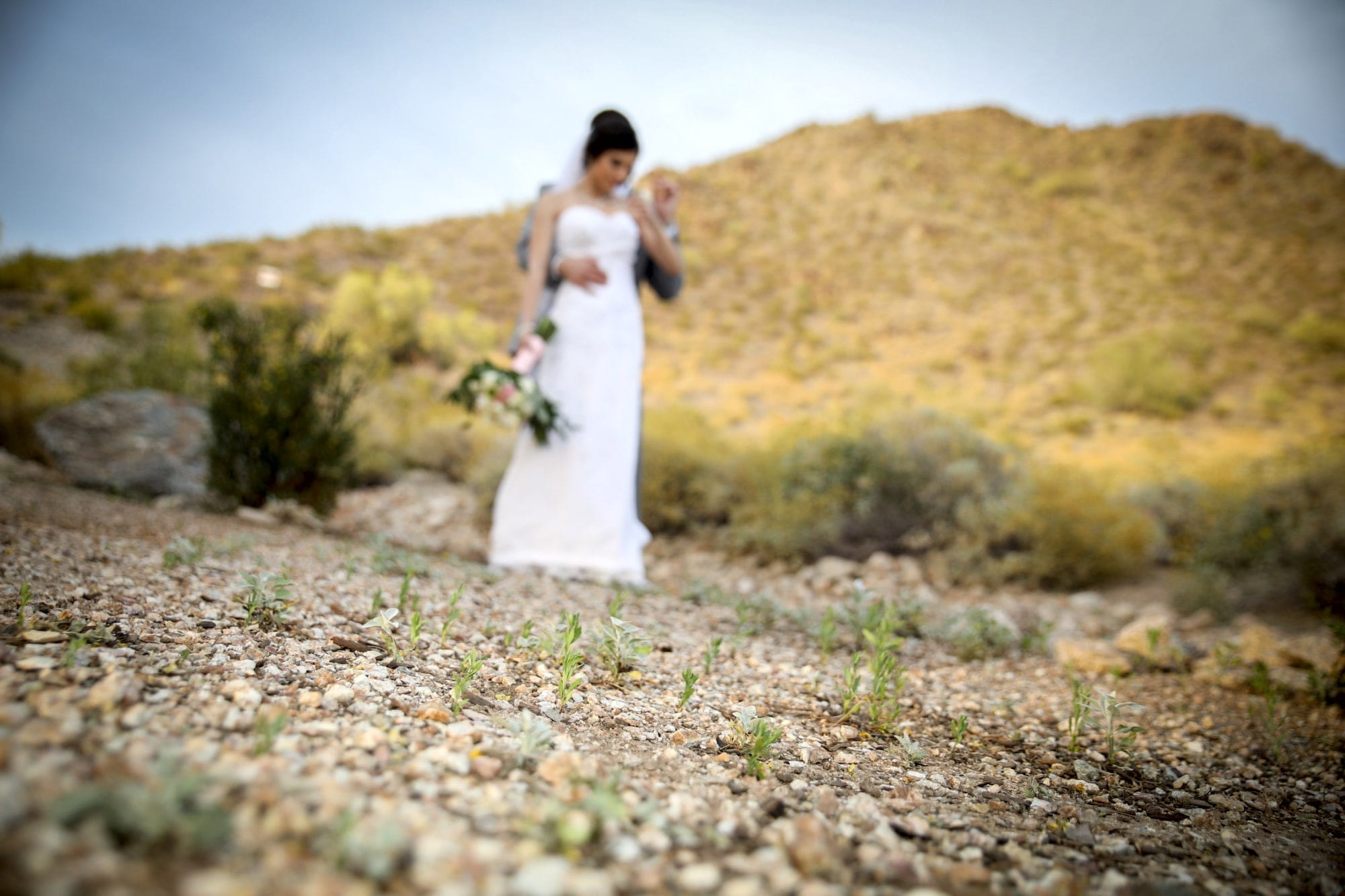 woman in white dress walking on dirt road during daytime