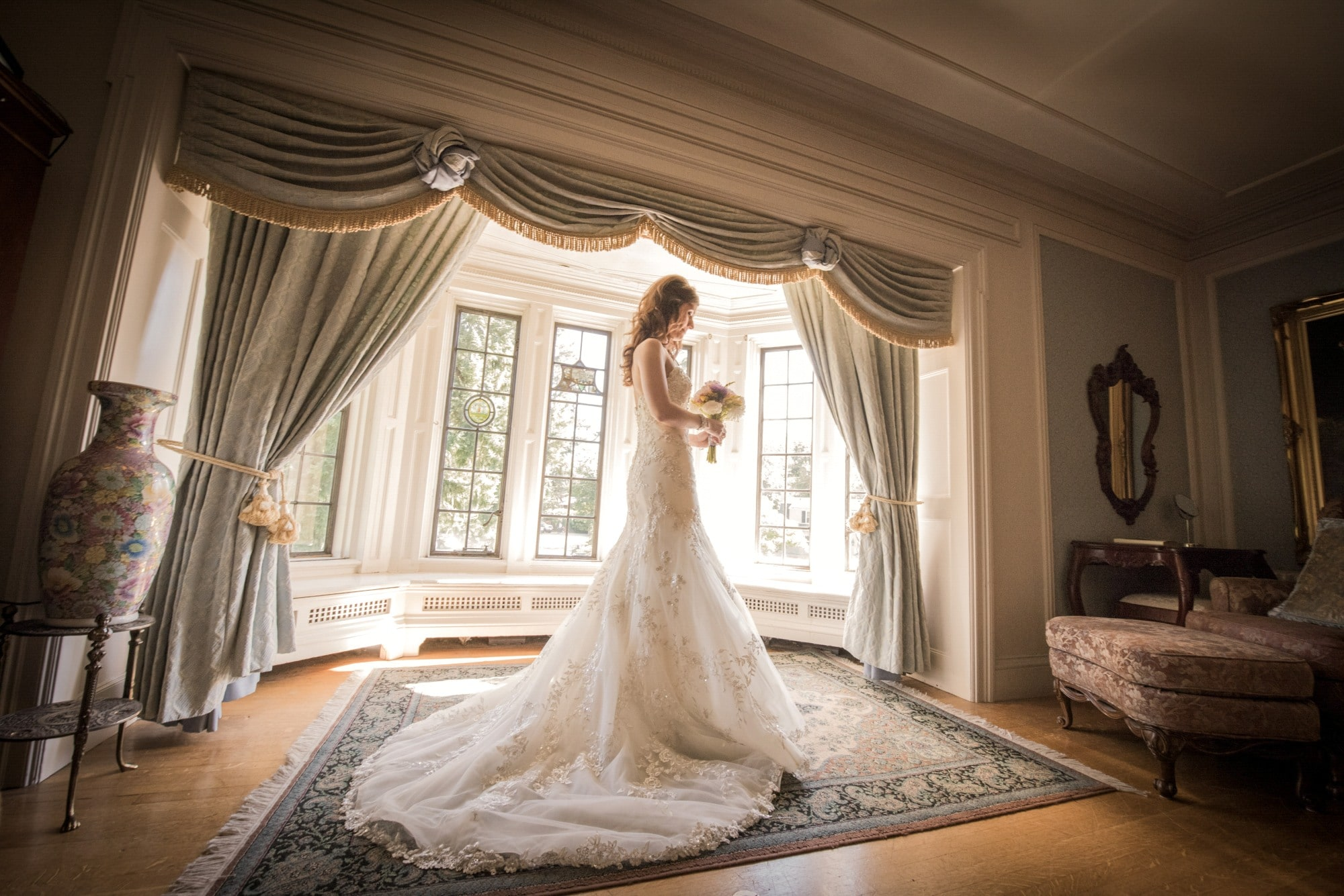 woman in white wedding dress standing on brown and white area rug