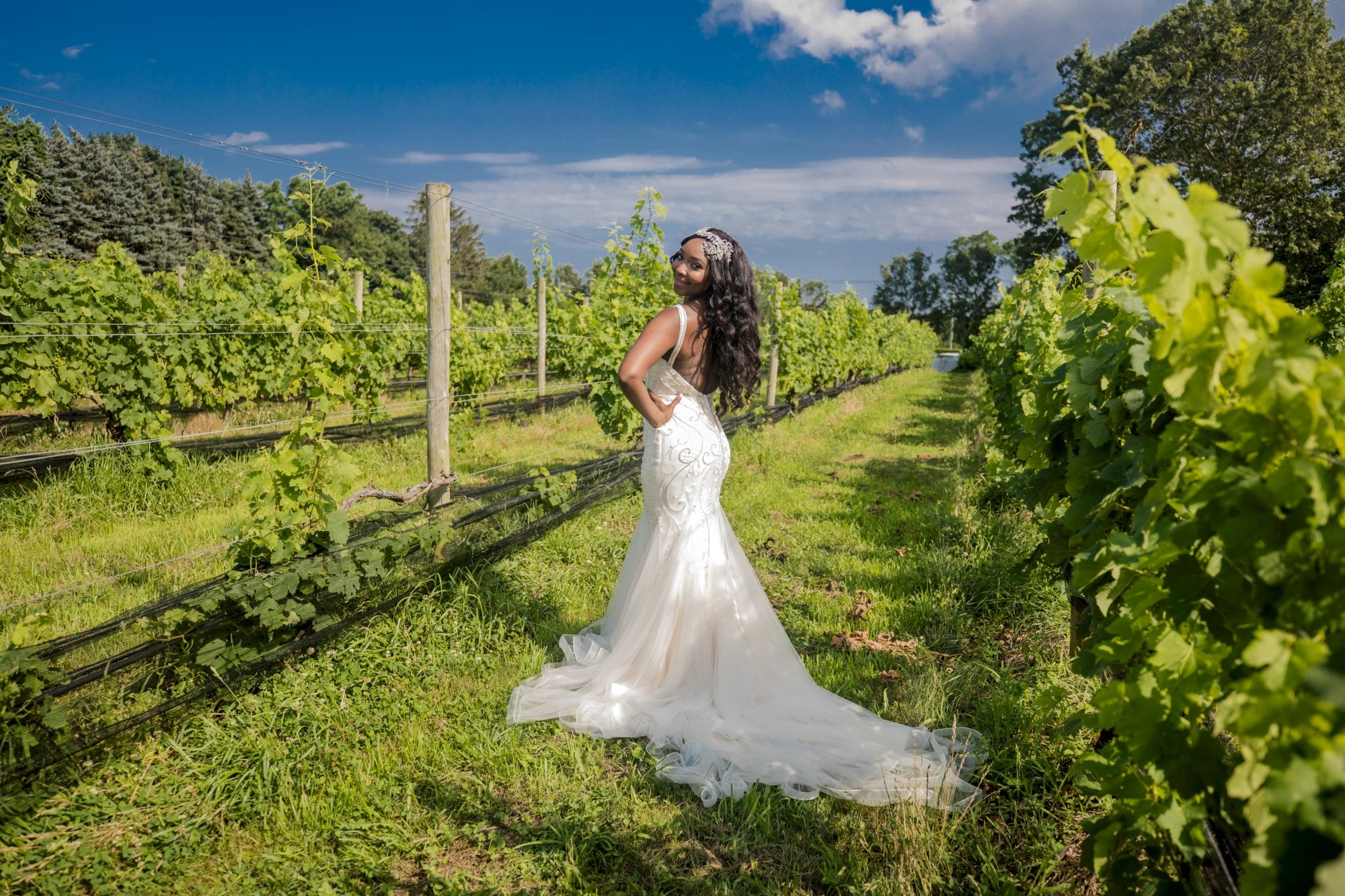 woman in white wedding gown standing on green grass field during daytime