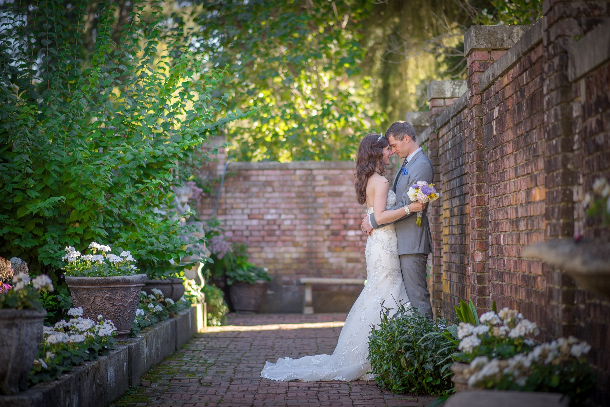 bride and groom standing on brick pathway during daytime