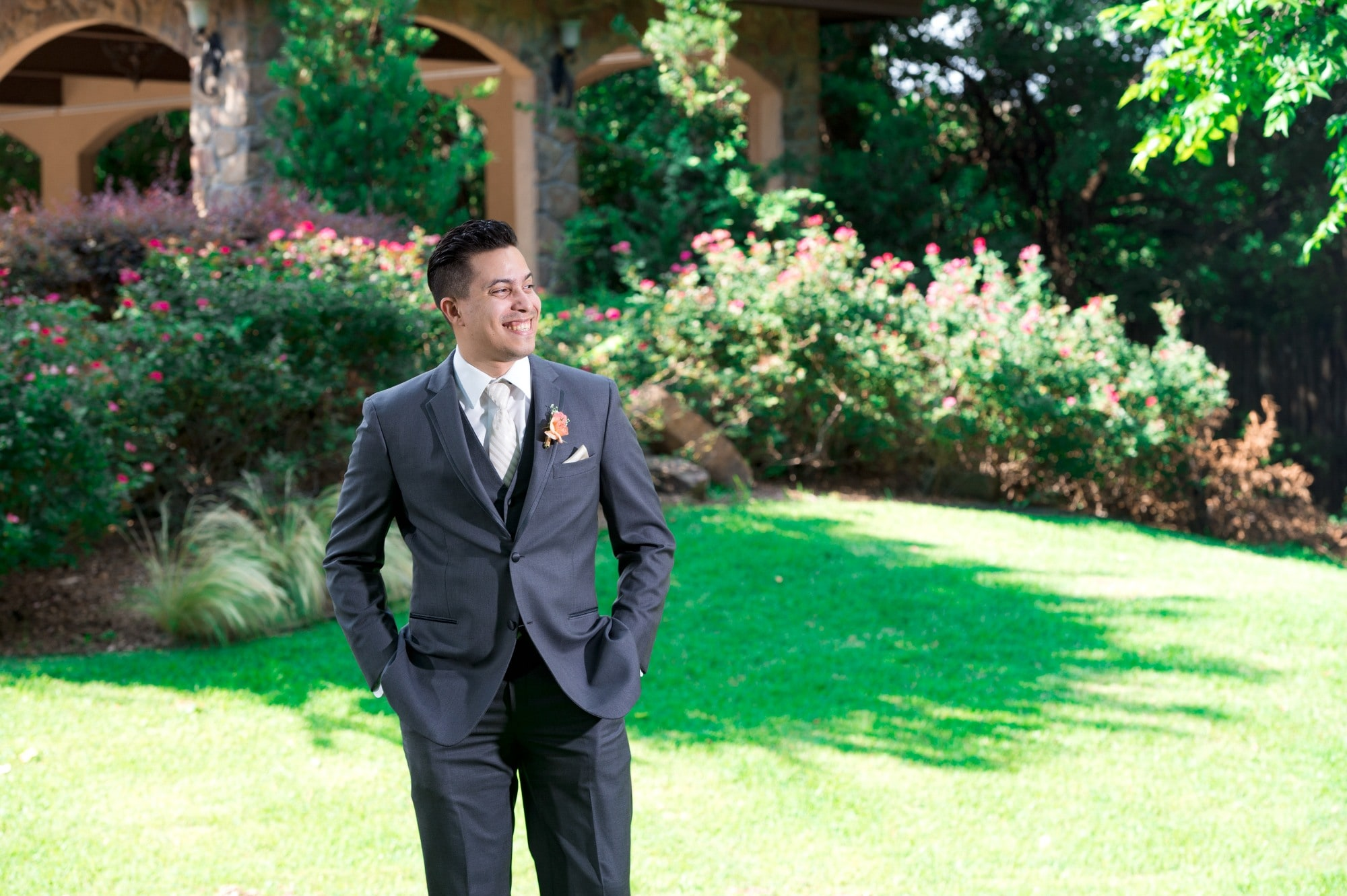 a man wearing a suit and tie standing in a garden